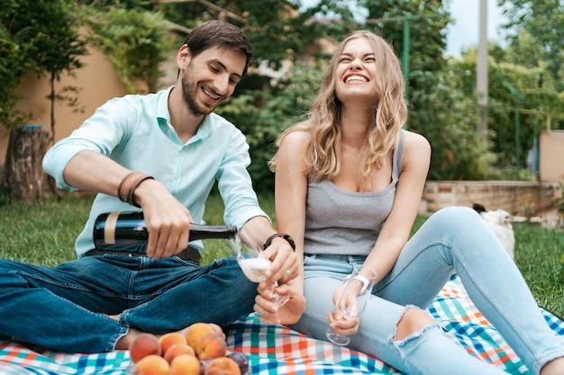 夏休み、人、ロマンス、デートのコンセプト、裏庭で家で一緒に時間を楽しみながらスパークリングワインを飲むカップル