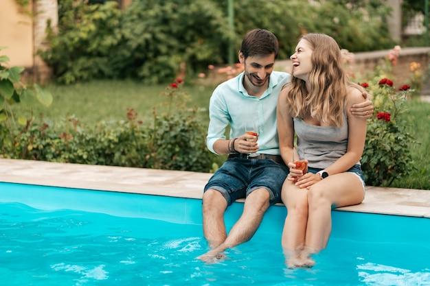夏休み、人、ロマンス、デートのコンセプト、一緒にプールに座って時間を楽しみながらスパークリングワインを飲むカップル
