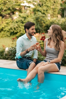 Summer holidays, people, romance, dating concept, couple drinking sparkling wine while enjoying time together sitting at the pool
