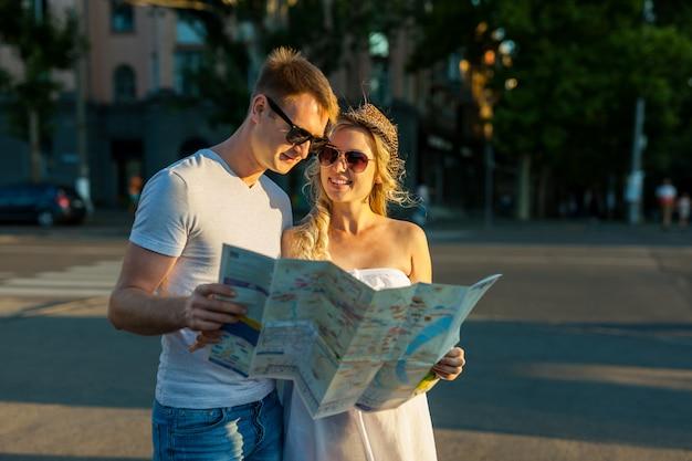 Летние каникулы - улыбающаяся пара в солнцезащитных очках с картой в городе