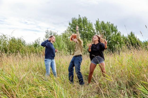 여름 휴가 휴가 행복 한 사람들 개념. 세 친구 소년과 두 여자 춤과 야외에서 함께 재미의 그룹