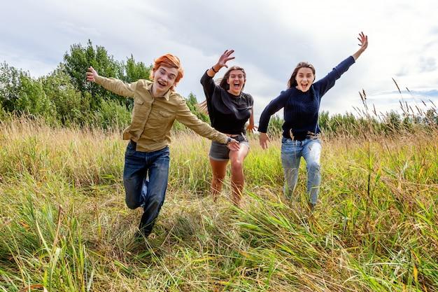 Летние каникулы каникулы счастливых людей концепции. группа из трех друзей мальчик и две девочки, бег и весело вместе на открытом воздухе.
