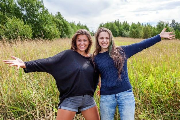 여름 휴가 휴가 행복한 사람들 개념. 두 여자 친구 자매의 그룹 포옹과 야외 자연에서 함께 즐거운 시간을 보내고 있습니다. 사랑스러운 순간 가장 친한 친구