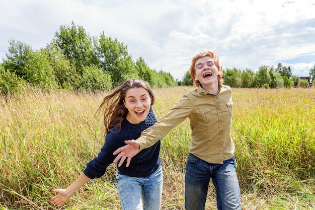 여름 휴가 휴가 행복한 사람들 개념. 야외에서 자연 속에서 함께 즐거운 시간을 보내는 사랑스러운 커플. 그의 여자 친구와 포옹 춤 행복 한 젊은 남자. 여름에 야외에서 행복한 사랑의 커플.