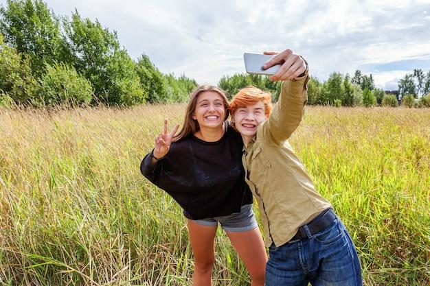 여름 휴가 휴가 행복한 사람들 개념. 야외에서 자연 속에서 함께 즐거운 시간을 보내는 사랑스러운 커플. 여자 친구와 함께 낭만적인 셀카를 찍고 행복 한 젊은 남자. 여름에 행복 한 사랑의 커플입니다.
