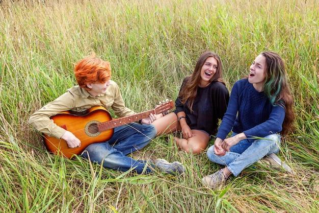 Летние каникулы каникулы музыка счастливые люди концепции. группа из трех друзей мальчик и две девушки с гитарой поют песню, весело вместе на открытом воздухе. пикник с друзьями в поездке на природу.