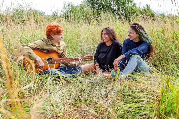 Summer holidays vacation music happy people concept. group of three friends boy and two girls with guitar singing song having fun together outdoors. picnic with friends on road trip in nature.