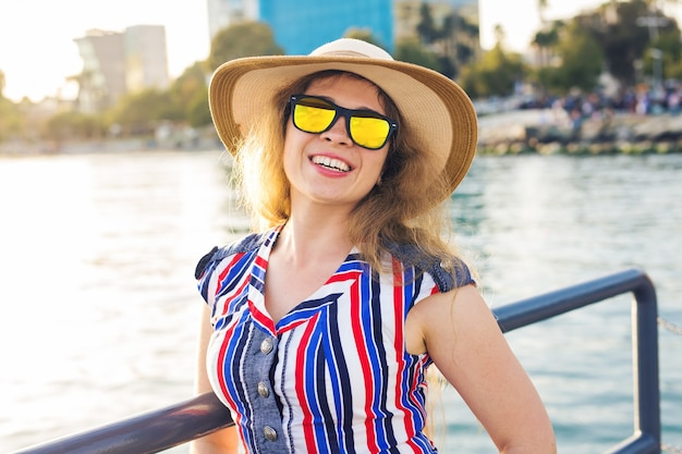 Summer holidays, vacation, travel and people concept - smiling laughing young woman wearing sunglasses and hat on beach over sea background.