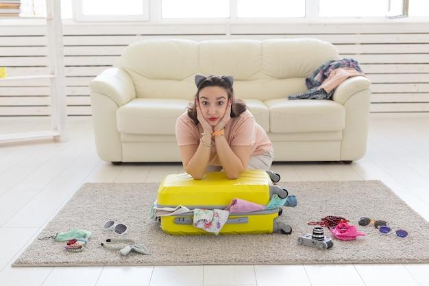 Летние каникулы, путешествие и концепция путешественника - молодая красивая женщина собирает чемодан летом