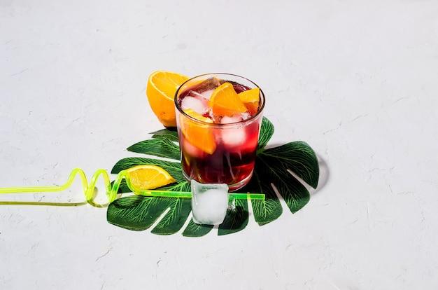 Летний домашний холодный красный коктейль из сангрии с апельсином и льдом в стакане на сером бетонном камне