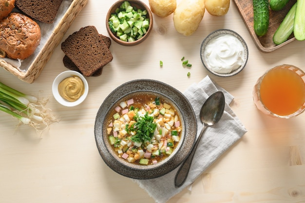 Летний домашний холодный суп свежести окрошка с квасом, сырыми нарезанными овощами, яйцами и ингредиентами на светлом деревянном фоне. вид сверху. скопируйте пространство. русская и украинская кухня.