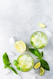 ライム、レモン、キュウリ、バジルを古いコンクリートの上にガラスの氷で作った夏の自家製レモネード。