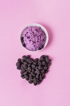 Summer ice cream in bowl with heart shape made out of blackberries