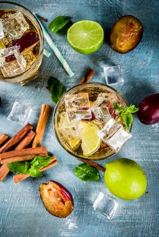 Summer iced refreshment drink. cinnamon and plum lemonade cocktail, with fresh lime and mint