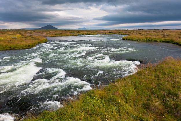 Летний пейзаж исландии с бушующей рекой в пасмурную погоду