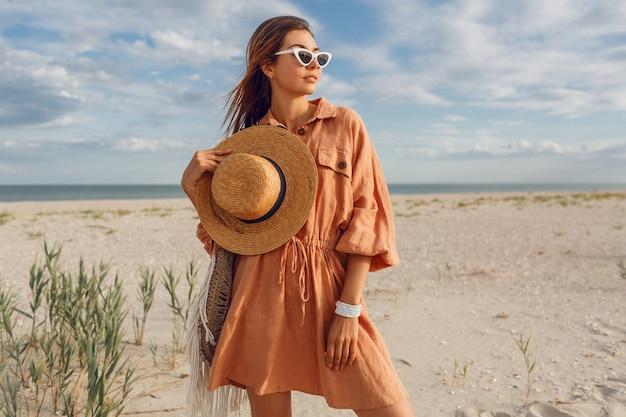Summer image of beautiful brunette female in trendy linen dress , holding straw bag. pretty slim girl enjoying weekends near ocean.