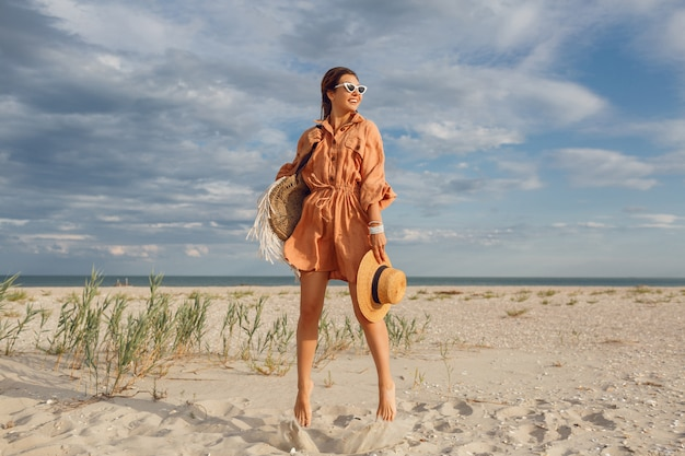 Summer image of beautiful brunette female in trendy linen dress jumping and fooling around , holding straw bag. pretty slim girl enjoying weekends near ocean. full length.