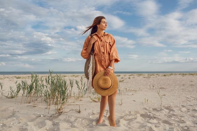 Immagine estiva di bella donna bruna in abito di lino alla moda che salta e scherza, tenendo il sacchetto di paglia. ragazza abbastanza magra che gode dei fine settimana vicino all'oceano.