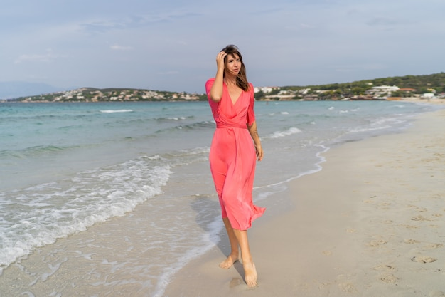 Summer image of happy sexy woman in gorgeous pink dress posing on the beach.  full lenght.