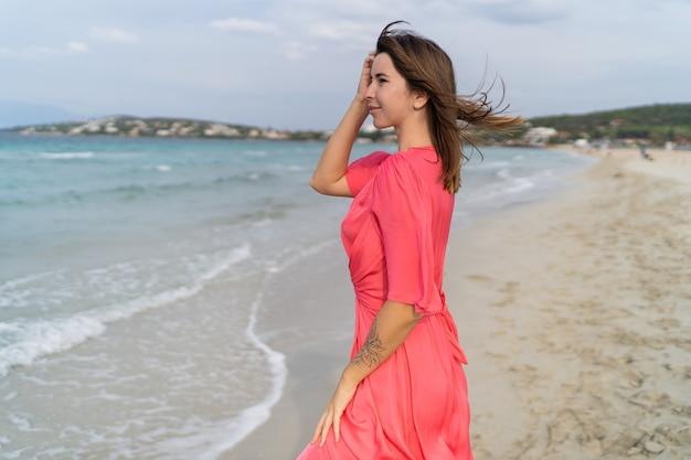 ビーチでポーズをとってゴージャスなピンクのドレスで幸せなセクシーな女性の夏の画像。