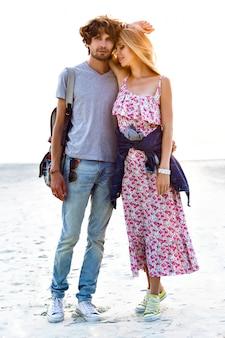 恋にロマンチックな甘いカップルの夏のイメージは抱擁し、明るい夕日の色、スタイリッシュな衣装を一緒に楽しんでいます。