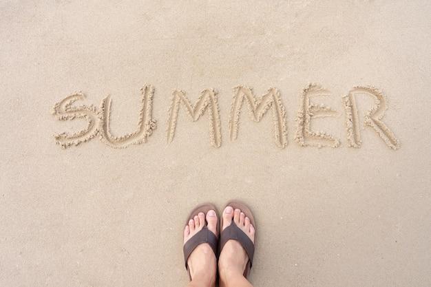 Summer is written on the sand of the sea beach.