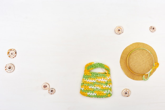 Summer items - sun hat, bag, towel on white.