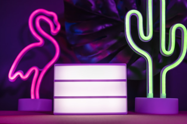 Summer items with flamingo and cactus and blank light box with neon pink and blue light on table