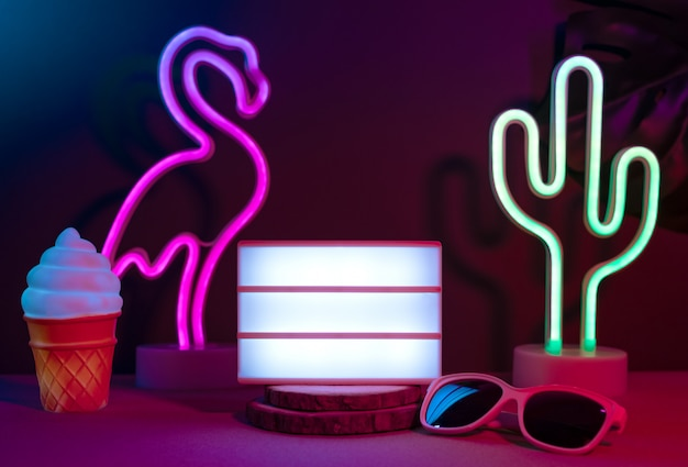 Summer items with flamingo, cactus, sunglasses and blank light box with neon pink and blue light on table with monstera leaf