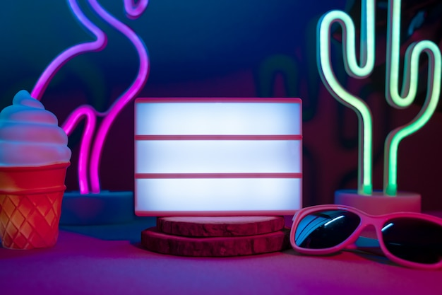 Summer items with flamingo, cactus, sunglasses and blank light box with neon pink and blue light on table