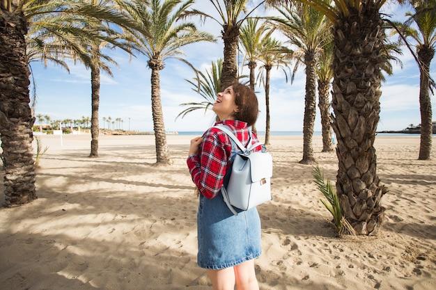 열 대 해변에서 야자수 아래 산책 여름 여행 및 여행 개념 젊은 여자