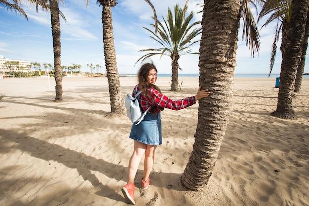 夏、旅、旅行のコンセプト-熱帯のビーチでヤシの木の下を歩く若い女性。