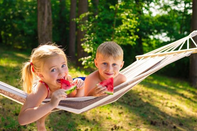 여름 joya 귀여운 소녀와 소년은 해먹에서 신선한 수박을 먹습니다