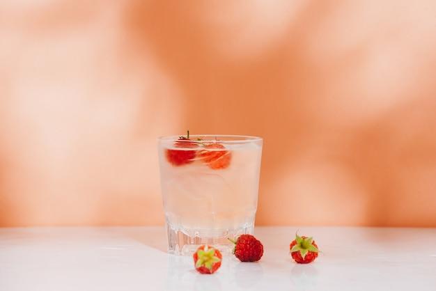 Летний сок со свежей малиной в стакане на светлом фоне