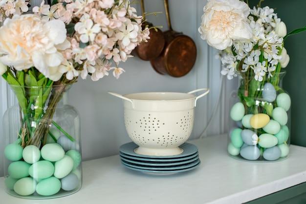 夏のキッチンのインテリア装飾白いザルプレートキッチンテーブルの上に花瓶の花の花束キッチンツール器具付きカウンタートップキッチン組織