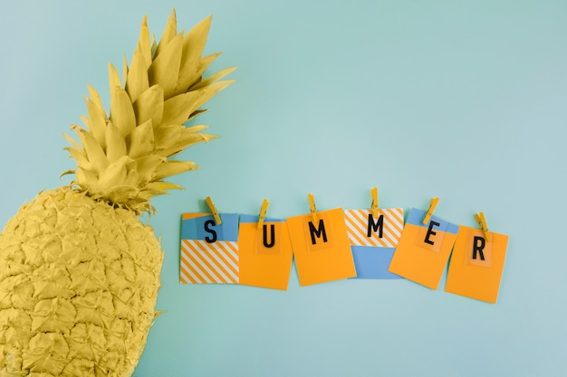 Summer label with clothespin near the painted yellow pineapple on blue background