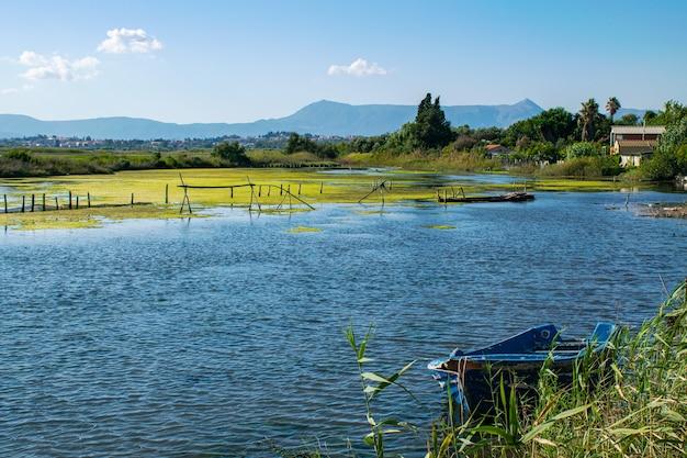Летнее озеро с грязью и синей лодкой на побережье корфу. ионический архипелаг. греция. европа