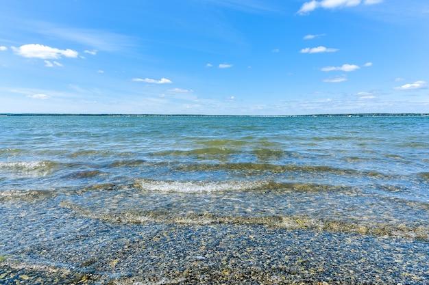Летний пейзаж. ясное озеро и голубое небо с облаками.