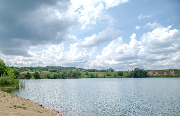 Summer landscape in the countryside with river, forest and clouds.