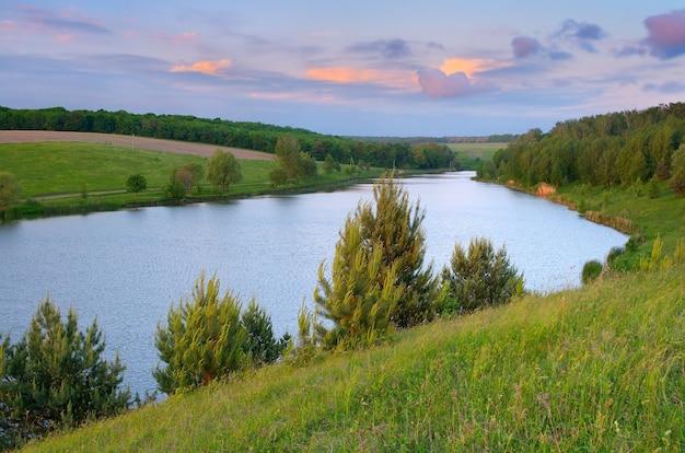 Летний пейзажный пруд. вечер с красивыми облаками