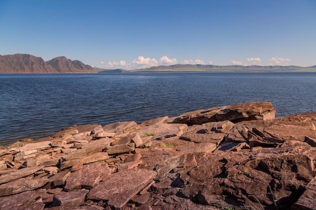 Летний пейзаж с водоем, каменистый берег на переднем плане и горы