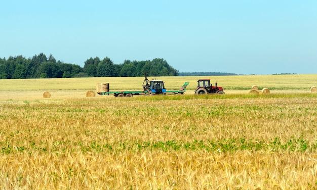 青い空と夏の風景。収穫中の農業機械と、農場に配送するためにトラクターに金の俵とわらの山を積み込みます。