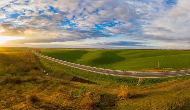 Летний пейзаж с зеленым полем с движением по дороге