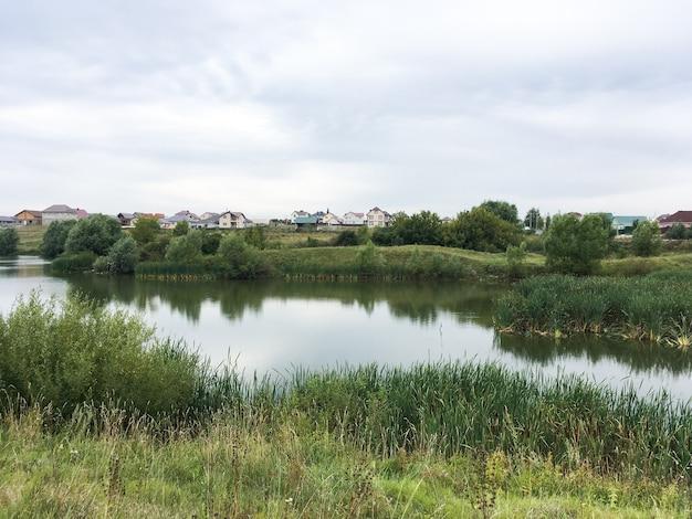 Летний пейзаж с зеленой травой и небольшим прудом 1