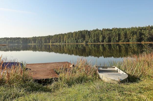 Летний пейзаж с озерным лесом на деревянной пристани горизонта неба и лодкой на берегу