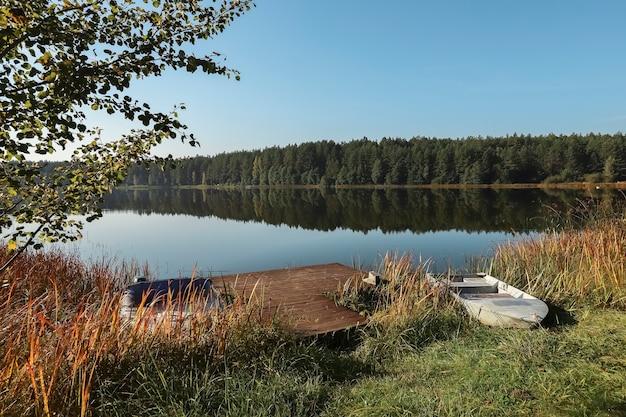 Летний пейзаж с озерным лесом на деревянной пристани горизонта неба и лодке