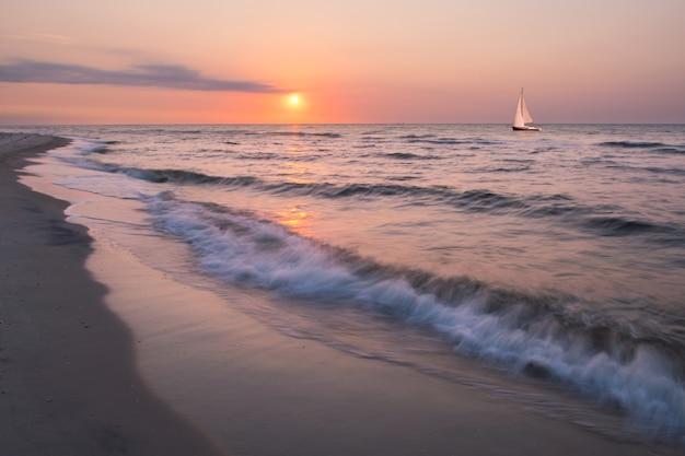 Летний пейзаж с одинокой яхтой на море, восход солнца с облаком, солнце в небе, морской пейзаж