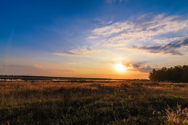 Summer landscape with meadow and beautiful sunset with forest and river