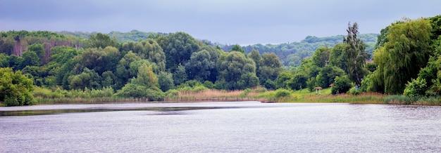 遠くに川と森のある夏の風景。湖のほとりの静かで穏やかな朝_