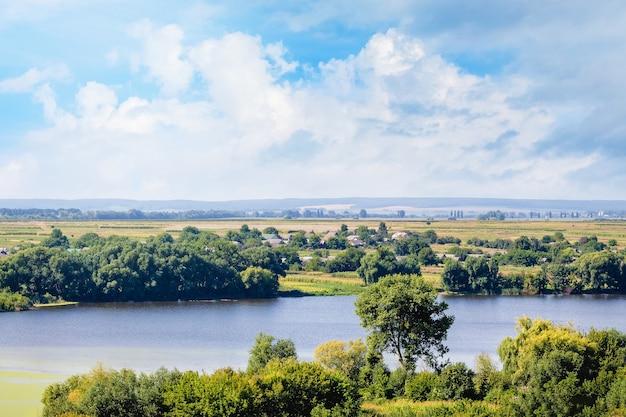 川、緑の海岸、白い雲と美しい空のある夏の風景_